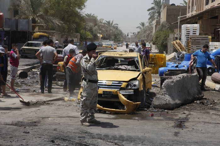 People inspect the aftermath of a car bomb attack in Baghdad's Shiite enclave of Sadr City, Iraq, Monday, July 23, 2012. An onslaught of bombings and shootings has killed scores of people across Iraq on Monday, in the nation's deadliest day so far this year. (AP Photo/Karim Kadim)