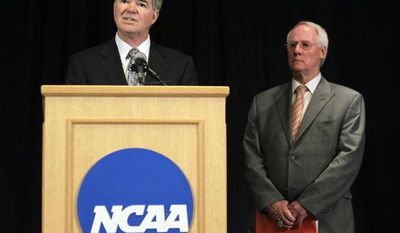 NCAA President Mark Emmert, left, announces penalties against Penn State as Ed Ray, NCAA Executive Committee chair and Oregon State University president, looks on at right, during a news conference in Indianapolis, Monday, July 23, 2012. (AP Photo/Michael Conroy)