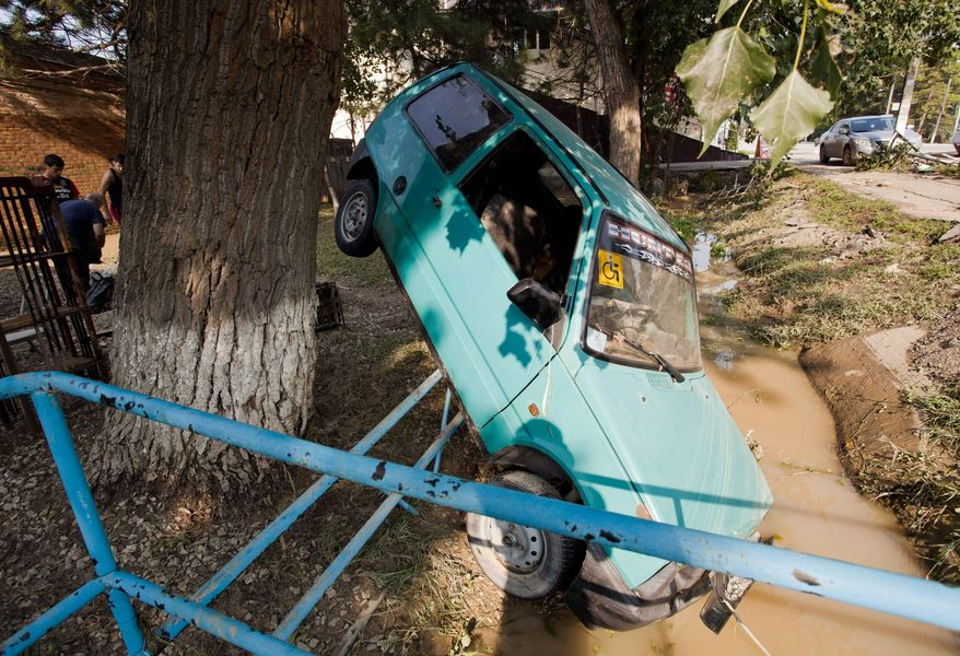 A damaged car suffered by flood seen next to a flooded house in Krimsk, about 1,200 kilometers (750 miles) south of Moscow, Russia, Sunday, July 8, 2012. The death toll from severe flooding in the Black Sea region of southern Russia has risen to at least 150. (AP Photo/Ignat Kozlov)