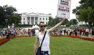 Vincent Leclercq of France demonstrates in front of the White House in Washington, Tuesday, July 24, 2012, as the AIDS conference continues in Washington. (AP Photo/Haraz N. Ghanbari)
