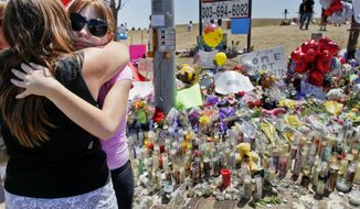 "Stacy Fleming, 23, second from left, hugs her friend Pam Frakes Monday, July 23, 2012, at a make-shift memorial that the public created across the street from the Century Theater where a mass shooting occurred last Friday killing 12 and injuring dozens of others in Aurora, Colo. Fleming and her boyfriend decided to go to another theater to watch ""The Dark Knight Rises"" at the last minute. (AP Photo/Barry Gutierrez)"