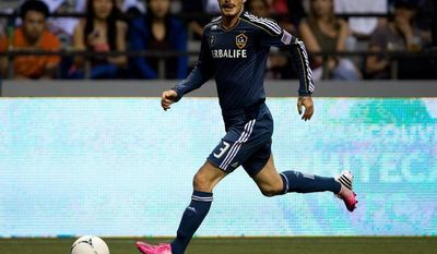 Los Angeles Galaxy's David Beckham, of England, carries the ball before setting up teammate Jose Villarreal's tying goal against the Vancouver Whitecaps during the second half of an MLS soccer game in Vancouver, British Columbia, on Wednesday, July 18, 2012.  (AP Photo/The Canadian Press, Darryl Dyck)