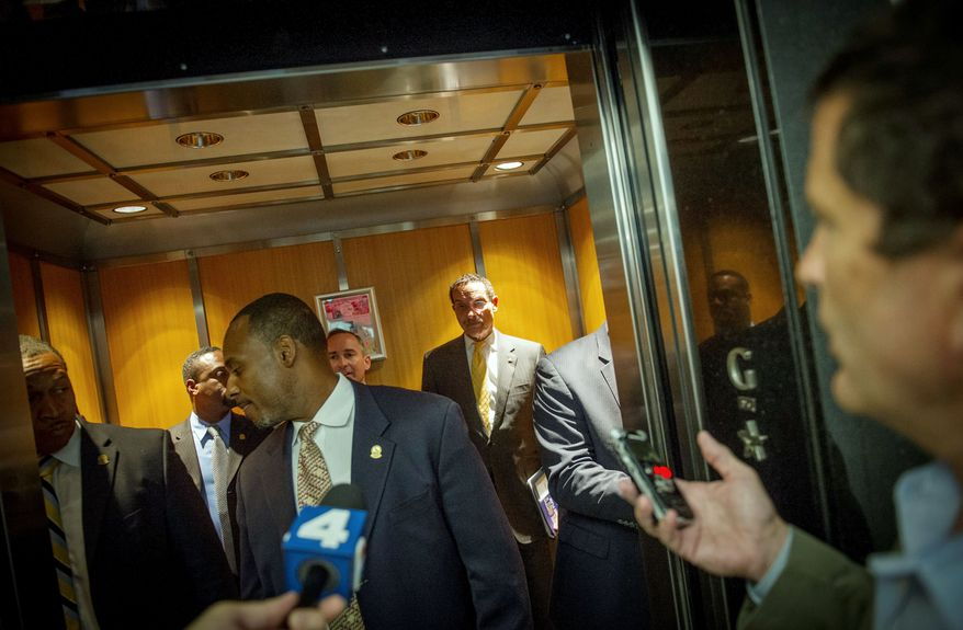 """Mayor Vincent C. Gray waits in an elevator as his staff and security detail rush him away from reporters after his announcement Wednesday of the """"One City Action Plan"""" which, like all of his actions in recent weeks, is set against the backdrop of scandal. (Rod Lamkey Jr./The Washington Times)"""