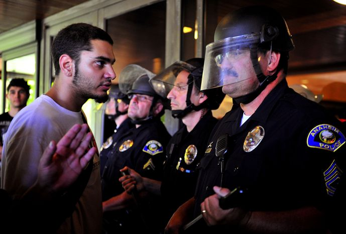 Demonstrators gather July 24, 2012, on the steps of Anaheim City Hall to protest the death of Manuel Diaz, 25, who died as a result of gunshot wounds sustained during a police pursuit by the Anaheim Police Department July 21. (Associated Press/The Orange County Register)
