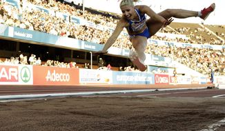 """FILE- Greece's Voula Papachristou soars through the air in the Women's Triple Jump final at the European Athletics Championships in Helsinki, Finland, in this file photo dated Friday, June 29, 2012. The Hellenic Olympic Committee has removed triple jumper Voula Papachristou from the team taking part in the upcoming London Olympic Games over comments she made on twitter making fun of African immigrants and expressing support for a far-right party. """"The track and field athlete Paraskevi (Voula) Papachristou is placed outside the Olympic Team for statements contrary to the values and ideas of the Olympic movement,"""" a statement by the Hellenic Olympic Committee says. Papachristou is in Athens, and was to travel to London """"shortly before the track events start,"""" the announcement says.(AP Photo/Matt Dunham, file)"""