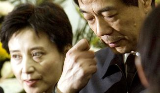 Chinese prosecutors have charged Gu Kailai — shown with her husband, former Chongqing Communist Party Secretary Bo Xilai — in the death of a British businessman who was poisoned in November, sparking a political scandal. (Associated Press)