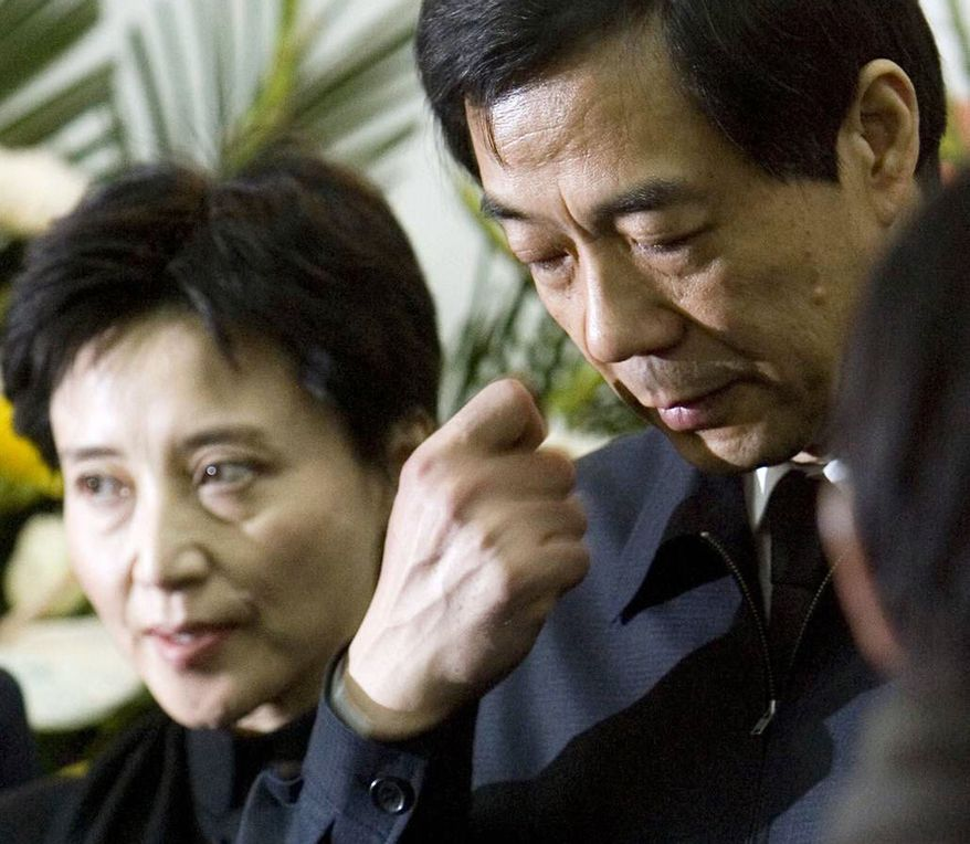 ** FILE ** In this Jan. 17, 2007, file photo, former Chongqing Communist Party Secretary Bo Xilai, right, accompanied by his wife Gu Kailai, attends a funeral for his father in Beijing. Chinese prosecutors were charging Gu and a family aide with the murder of a British businessman, the official Xinhua News Agency reported Thursday, July 26, 2012. (AP Photo/Kyodo News/China Foto Press)