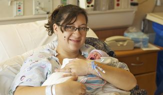 ** FILE ** In this photo provided by the University of Colorado Hospital, Katie Medley holds her newborn son Hugo Jackson Medley at the hospital in Aurora, Colo, Tuesday, July 24, 2012. When Mrs. Medley gave birth to the healthy baby boy, her husband Caleb, wounded in Colorado's theater shooting, lay in a medically-induced coma one floor below her. Hugo Jackson was born at 7:11 a.m. MT. Tuesday, hospital spokesman Dan Weaver said. (AP Photo/University of Colorado Hospital)