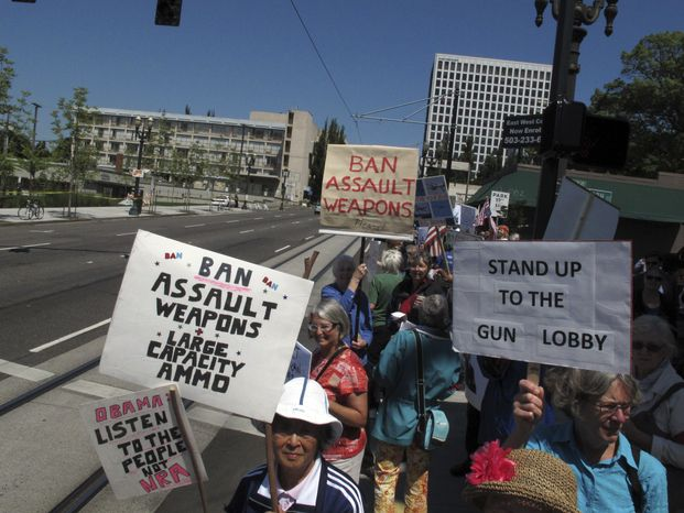 **FILE** Advocates demanding tougher gun control laws were among several dozen protesters who greeted President Obama outside the Oregon Convention Center in Portland, Ore., on July 24, 2012. Obama was in Oregon to raise money for his re-election campaign. (Associated Press)