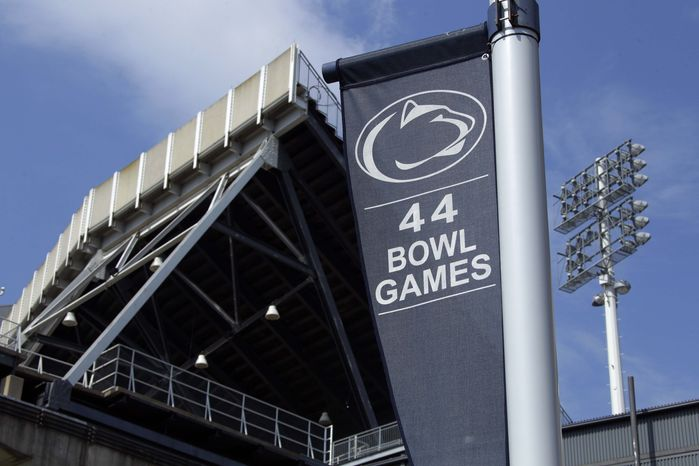 **FILE** A banner celebrating the 44 bowl games that the Penn State football team has played in hangs outside of Beaver Stadium on the Penn State University main campus in State College, Pa., on July 23, 2012. (Associated Press)