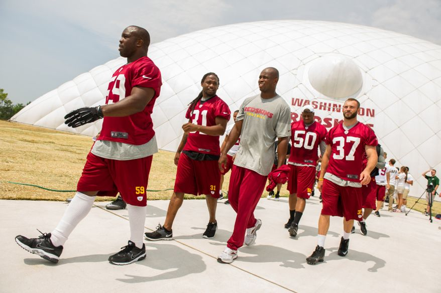 Washington Redskins linebacker London Fletcher (59), left, and other players leave the indoor training dome as the Washington Redskins finish morning walk-throughs on the first day of training camp at Redskins Park, Ashburn, Va., Thursday, July 26, 2012. (Andrew Harnik/The Washington Times)