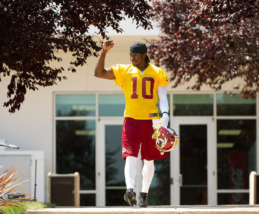 Washington Redskins quarterback Robert Griffin III (10) pumps his fist for the cheering crowd of Washington Redskins fans as he takes the field for afternoon practice on the first day of training camp at Redskins Park, Ashburn, Va., Thursday, July 26, 2012. (Andrew Harnik/The Washington Times)