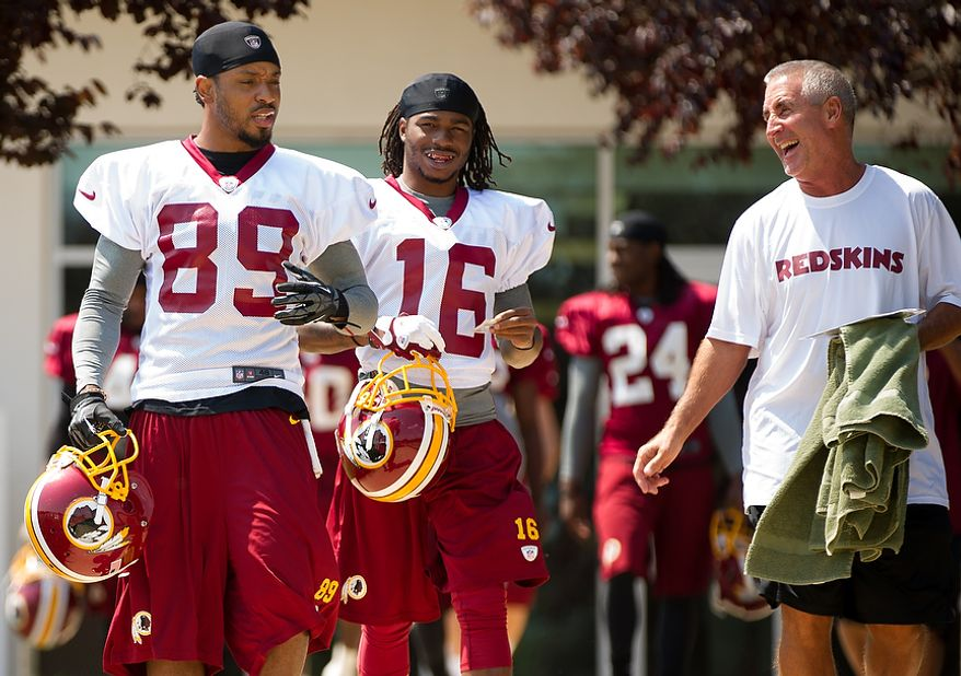 Washington Redskins wide receiver Santana Moss (89), left, wide receiver Brandon Banks (16), center, and special teams coach Danny Smith, right, make their way to the field for afternoon practice on the first day of training camp at Redskins Park, Ashburn, Va., Thursday, July 26, 2012. (Andrew Harnik/The Washington Times)
