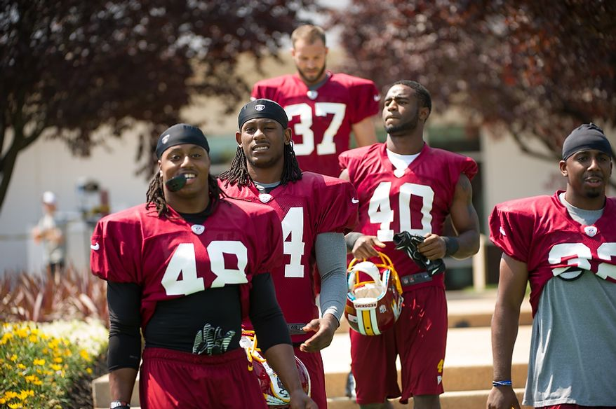 Left to right: Washington Redskins cornerback Jordan Bernstine (48),  defensive back DeJon Gomes (24), defensive back Reed Doughty (37), and defensive back Travon Bellamy (40), make their way to the field for afternoon practice on the first day of training camp at Redskins Park, Ashburn, Va., Thursday, July 26, 2012. (Andrew Harnik/The Washington Times)