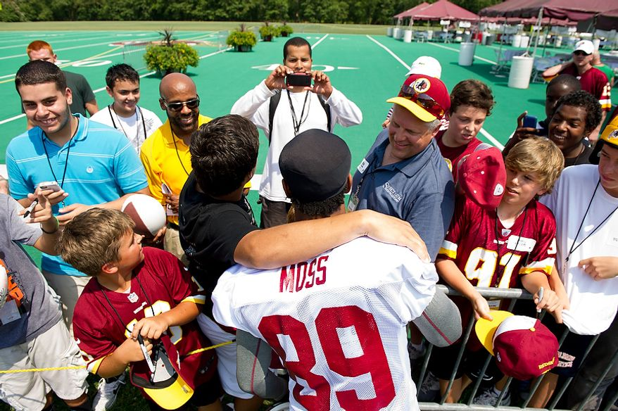 Laith Hasanian, 15, of Oakhill, Va., gets his photo taken with Washington Redskins wide receiver Santana Moss (89) as he makes his way to the field for afternoon practice on the first day of training camp at Redskins Park, Ashburn, Va., Thursday, July 26, 2012. (Andrew Harnik/The Washington Times)