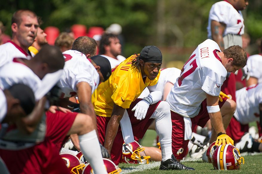 Washington Redskins quarterback Robert Griffin III (10), center, stretches during afternoon practice on the first day of training camp at Redskins Park, Ashburn, Va., Thursday, July 26, 2012. (Andrew Harnik/The Washington Times)