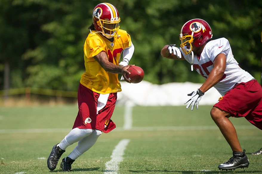Washington Redskins quarterback Robert Griffin III (10), left, fakes a hand off to running back Evan Royster (35), right, during afternoon practice on the first day of training camp at Redskins Park, Ashburn, Va., Thursday, July 26, 2012. (Andrew Harnik/The Washington Times)