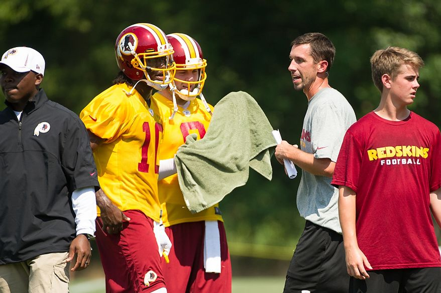 Washington Redskins quarterback Robert Griffin III (10), second from left, and quarterback Rex Grossman (8), center, talk with offensive coach Kyle Shanahan, second from right, during afternoon practice on the first day of training camp at Redskins Park, Ashburn, Va., Thursday, July 26, 2012. (Andrew Harnik/The Washington Times)