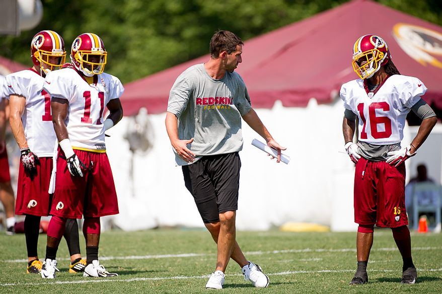 Washington Redskins offensive coach Kyle Shanahan, center, works with wide receiver Brandon Banks (16), right, and wide receiver Aldrick Robinson (11), second from left, and other wide receivers during afternoon practice on the first day of training camp at Redskins Park, Ashburn, Va., Thursday, July 26, 2012. (Andrew Harnik/The Washington Times)