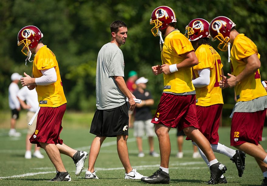 Washington Redskins quarterback run past offensive coach Kyle Shanahan, center, during afternoon practice on the first day of training camp at Redskins Park, Ashburn, Va., Thursday, July 26, 2012. (Andrew Harnik/The Washington Times)