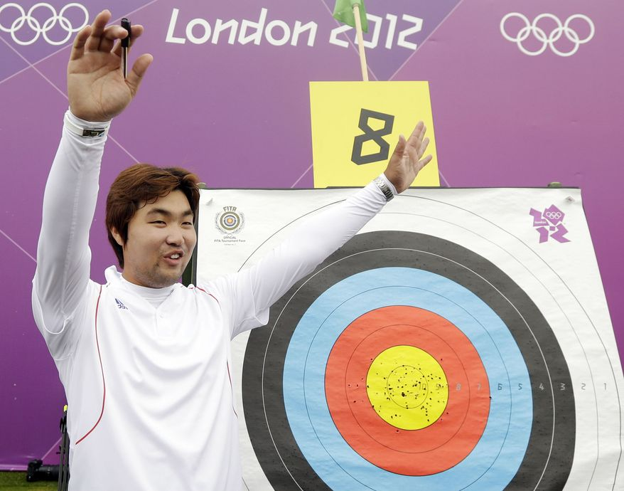 South Korea's Im Dong-hyun celebrates his world record during an individual ranking round at the 2012 London Olympics, Friday, July 27, 2012. Dong-hyun set world record in the round with a 699 score. (AP Photo/Marcio Jose Sanchez)