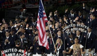 Fencer Mariel Zagunis leads Team USA into the stadium during the Opening Ceremony for the 2012 Olympic Summer Games, Friday, July 27, 2012, in London. (AP Photo/The Canadian Press, Sean Kilpatrick)