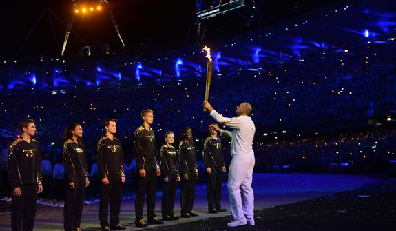 Sir Steve Redgrave carries the torch into the stadium during the Opening Ceremony for the London Olympic Games, Saturday, July 28, 2012, in London.  (AP Photo/Owen Humphreys,  PA) UNITED KINGDOM OUT; NO SALES; NO ARCHIVE