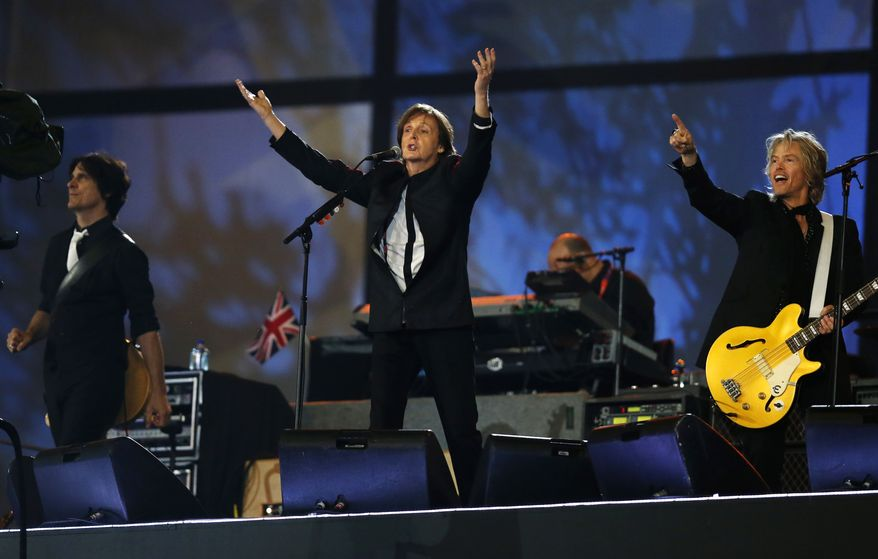 Paul McCartney, center, performs during the Opening Ceremony at  the 2012 Summer Olympics, Saturday, July 28, 2012, in London. (AP Photo/Matt Dunham, Pool)