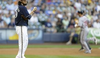 Milwaukee Brewers starting pitcher Yovani Gallardo looks away as Washington Nationals' Adam LaRoche rounds the bases on a home run during the second inning of a baseball game Thursday, July 26, 2012, in Milwaukee. (AP Photo/Jeffrey Phelps)