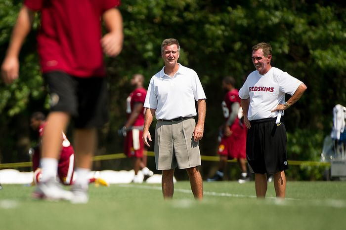 Washington Redskins general manager Bruce Allen, left, talks with  head coach Mike Shanahan, right, during afternoon practice on the first day of training camp at Redskins Park, Ashburn, Va., Thursday, July 26, 2012. (Andrew Harnik/The Washington Times)