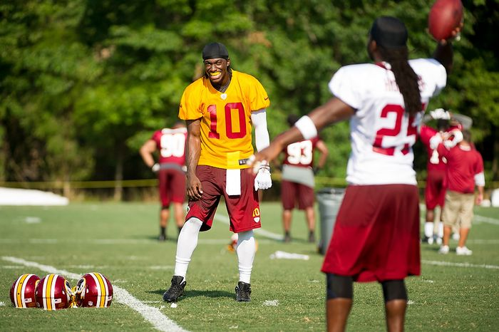 Washington Redskins quarterback Robert Griffin III (10), center, throws with running back Tim Hightower (25), right, following afternoon practice on the first day of training camp at Redskins Park, Ashburn, Va., Thursday, July 26, 2012. (Andrew Harnik/The Washington Times)