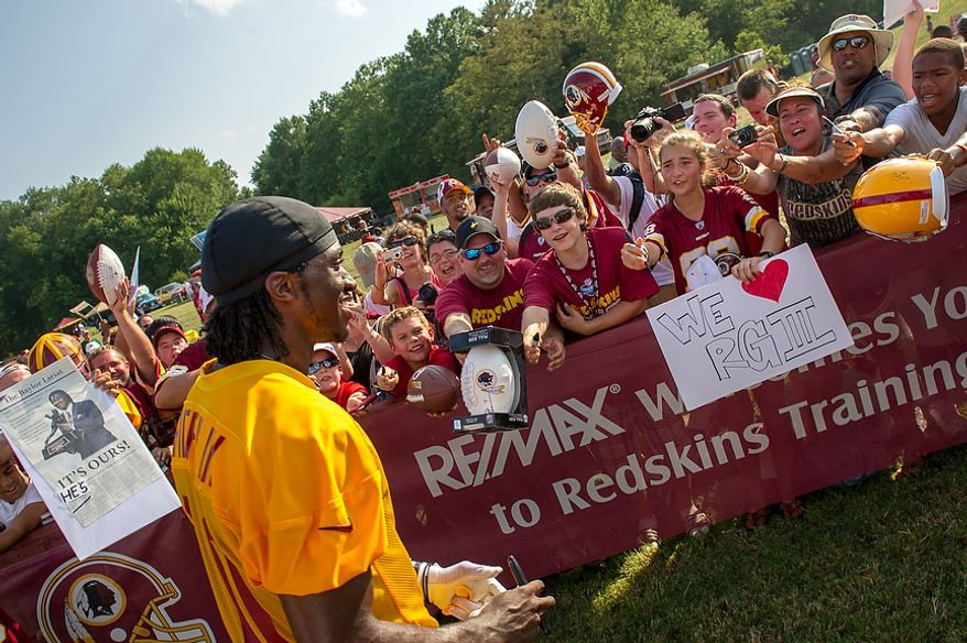 Washington Redskins quarterback Robert Griffin III (10) makes his way over to screaming fans following afternoon practice on the first day of training camp at Redskins Park, Ashburn, Va., Thursday, July 26, 2012. (Andrew Harnik/The Washington Times)