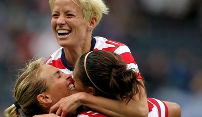 United States' Carli Lloyd, right, celebrates her third goal with teammates Megan Rapinoe, top, and Heather Mitts during the women's group G soccer match against Colombia at Hampden Park, in Glasgow, Scotland on Saturday, July 28, 2012. (AP Photo/Lynne Cameron, PA) UNITED KINGDOM OUT; NO SALES; NO ARCHIVE