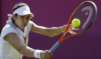 Christina McHale of the United States returns a shot to Ana Ivanovic at the All England Lawn Tennis Club at Wimbledon, in London, at the 2012 Summer Olympics, Saturday, July 28, 2012. (AP Photo/Mark Humphrey)
