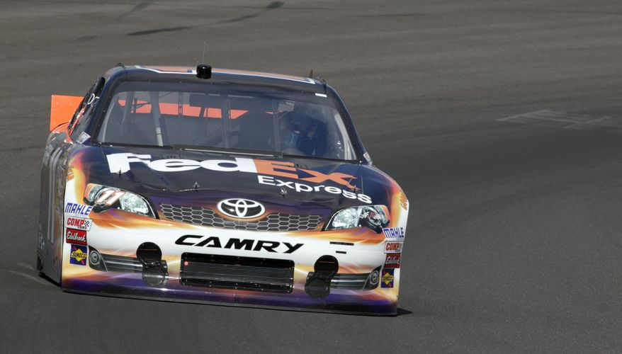 Denny Hamlin drives out of the first turn during practice for Sunday's NASCAR Sprint Cup Series auto race at the Indianapolis Motor Speedway in Indianapolis, Saturday, July 28, 2012. Hamlin won the pole for the race. (AP Photo/AJ Mast)