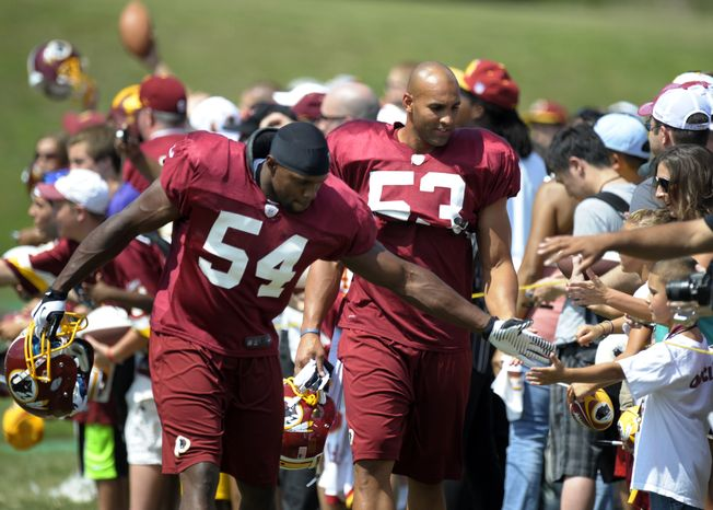 Washington Redskins linebackers Jonathan Goff, left, and Bryan Kehl greet fans as they walk to a practice field during NFL football training camp at Redskins Park in Ashburn, Va., Saturday, July 28, 2012. (AP Photo/Cliff Owen)