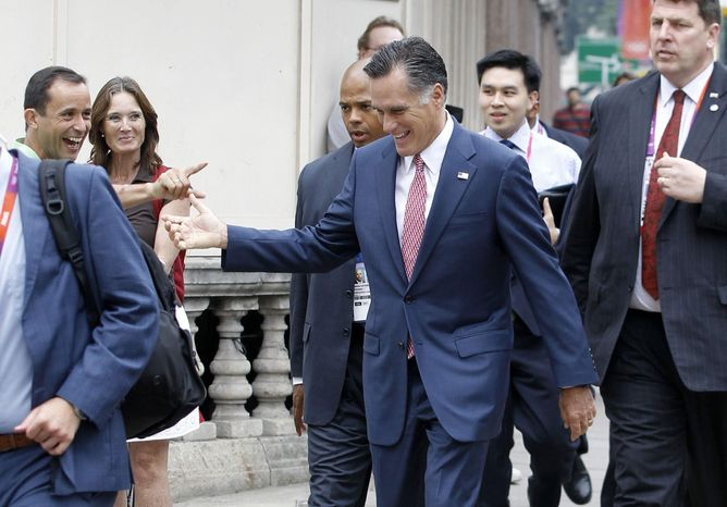 Avoiding a traffic jam, Republican presidential candidate, former Massachusetts Gov. Mitt Romney is recognized by a bystander as he walks down Grosvenor Place to meet Ireland's Prime Minister Enda Kenny at the Embassy of Ireland in London, Friday, July 27, 2012. (AP Photo/Charles Dharapak)