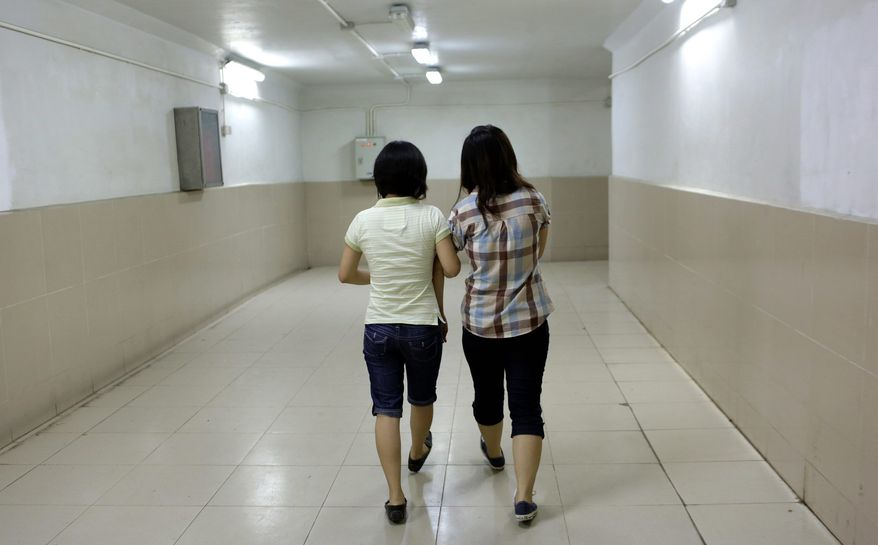 Dinh Thi Hong Loan, 30, (left) holds the hand of her girlfriend, Nguyen Thi Chi, 20, as they walk down a corridor in Hanoi. The lesbian couple have dated for more than two years and plan to marry. (Associated Press)