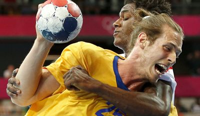 Sweden's Kim Ekdahl du Rietz, foreground is tackled by Tunisia's Wael Jallouz, background, in their men's handball preliminary match at the 2012 Summer Olympics, Sunday, July 29, 2012, in London. (AP Photo/Vadim Ghirda)