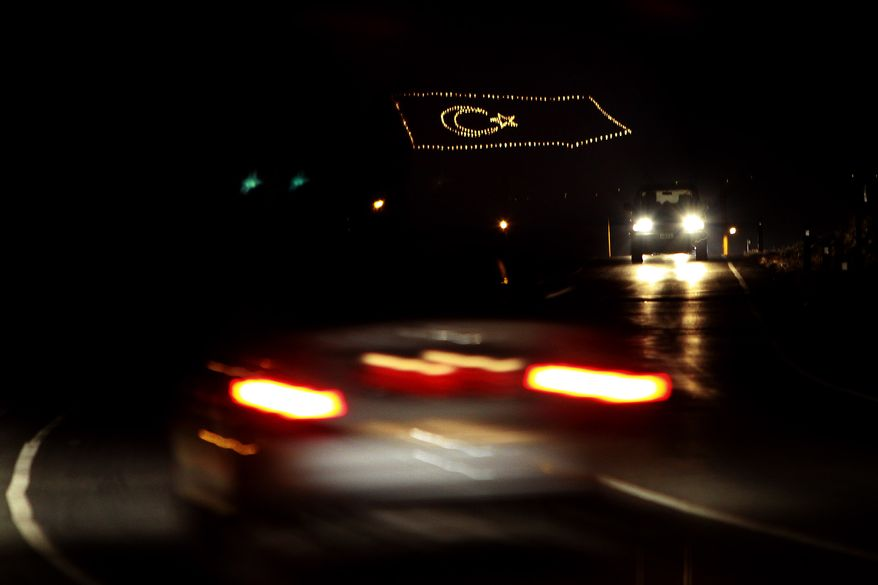 **FILE** A giant Turkish flag is illuminated July 18, 2012, on the Pentadaktilos mountain in the Turkish-occupied area in Nicosia, Cyprus, as cars pass on the road. (Associated Press)