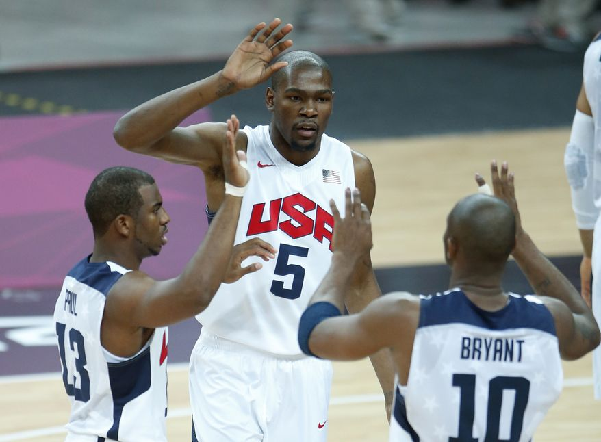 USA's Kevin Durant (5), Chris Paul (13) and Kobe Bryant (10) react during the first half of a preliminary men's basketball game against France at the 2012 Summer Olympics, Friday, July 27, 2012, in London. (AP Photo/Jae C. Hong)