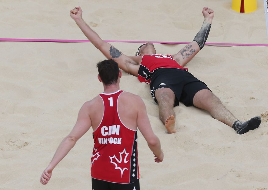 Josh Binstock, left, from Canada and his teammate Martin Reader, right, celebrate after defeating team Great Britain in their Beach Volleyball match at the 2012 Summer Olympics, Saturday, July 28, 2012, in London. (AP Photo/Petr David Josek)