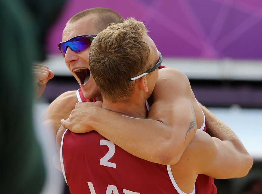 Martins Plavins, left, from Latvia celebrates with his teammate Janis Smedins, right, after defeating Germany in their Beach Volleyball match at the 2012 Summer Olympics, Sunday, July 29, 2012, in London. (AP Photo/Petr David Josek)