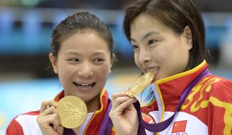London 2012 diving: Gold medalists He Zi, left, and Wu Minxia, right, pose with their medals after the 3 Meter Synchronized Springboard final at the Aquatics Centre in the Olympic Park on Sunday, July 29, 2012. (AP Photo/Mark J. Terrill)