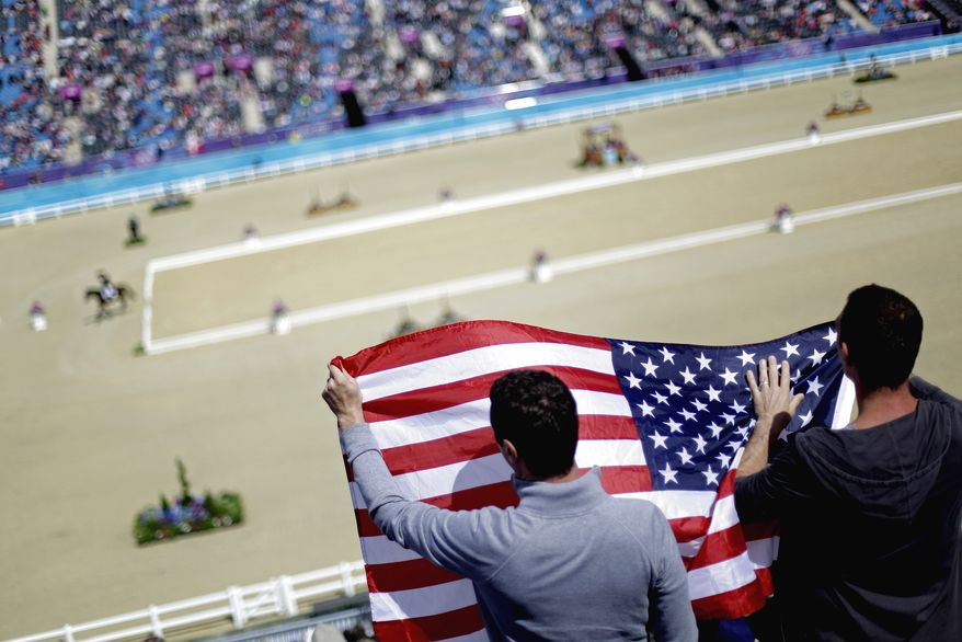 Fans cheer as Phillip Dutton of the United States exits the ring after competing with his horse Mystery Whisper in the equestrian eventing dressage phase at the 2012 Summer Olympics, Sunday, July 29, 2012, in London. (AP Photo/David Goldman)