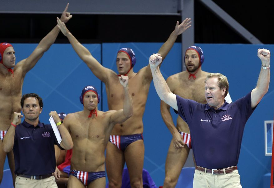 United States men's water polo athletes react with coach Terry Schroeder, right, after beating Montenegro 8-7 in a preliminary water polo match at the 2012 Summer Olympics, Sunday, July 29, 2012, in London. (AP Photo/Julio Cortez)