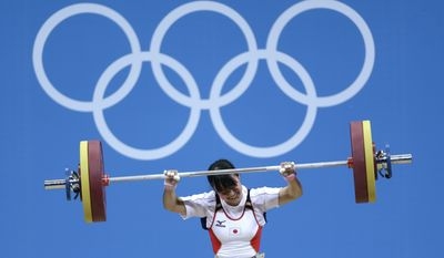 Japan's Kanae Yagi lifts during the women's 53-kg, group B, weightlifting competition at the 2012 Summer Olympics, Sunday, July 29, 2012, in London. (AP Photo/Mike Groll)