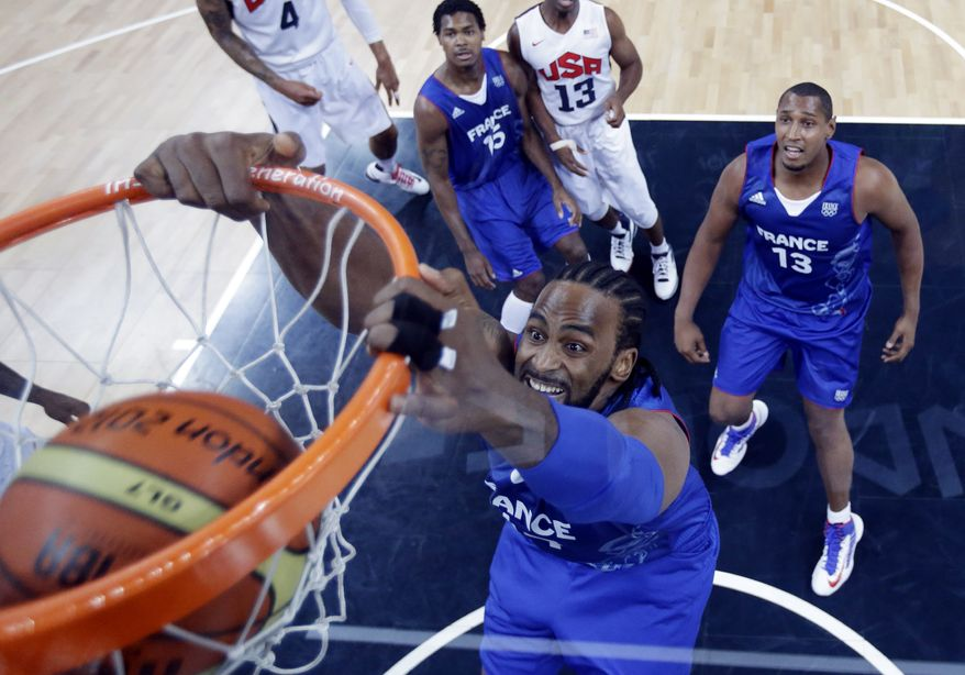 France's Ronny Turiaf scores as teammates  Boris Diaw and Mickael Gelabale look on during the first half of a preliminary men's basketball game against the USA at the 2012 Summer Olympics, Sunday, July 29, 2012, in London. (AP Photo/Eric Gay, pool)
