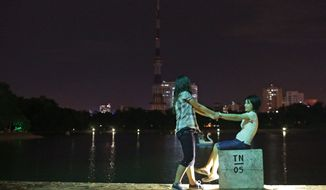 Nguyen Thi Chi (left), 20, plays July 26, 2012, with her girlfriend Dinh Thi Hong Loan, 30, at Thong Nhat park in Hanoi, Vietnam. The lesbian couple have dated for more than 2 years and plan to get married next month. (Associated Press)