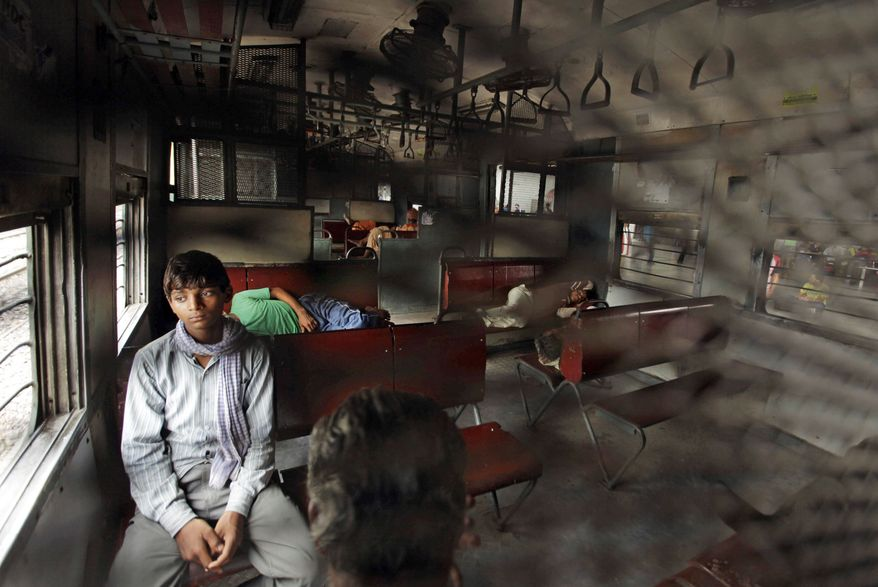 An Indian passenger waits for the power to return as others sleep inside the compartment of a stationary train in New Delhi on Monday after a power outage. The outage struck northern India, plunging cities into darkness, stranding commuters and leaving 370 million sweltering in the summer heat. (Associated Press)
